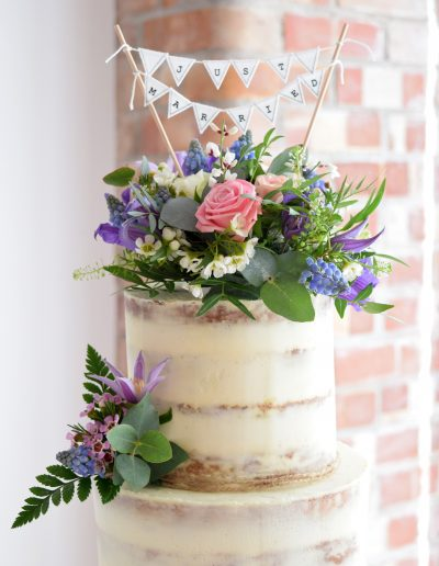 Semi naked cake dressed with fresh blooms from Escential Blooms