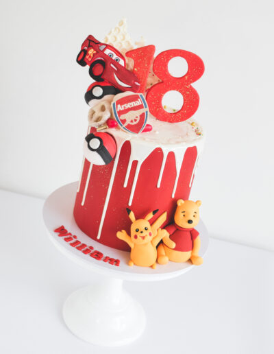 18th Birthday cake - Red fondant finished cake with a white chocolate drip. Handcrafted pokemon balls, pokemon characters, pooh bear, arsenal football and Cars items featured on the cake.