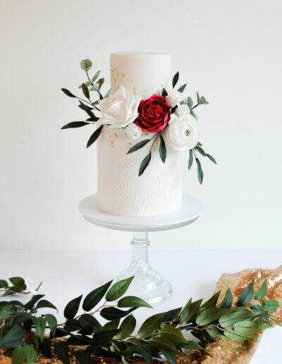 Two tier wedding cake decorated with sugar blooms and foliage