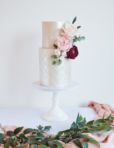 Two tier wedding cake. Extended base tier with quilting effect. Lustred finished cake dressed with hancrafted sugar blooms