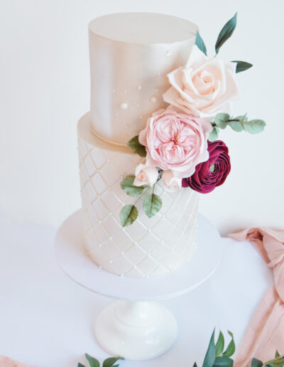 Close up image of sugar flowers, david austin roses, sweet avalanche and ranunculus