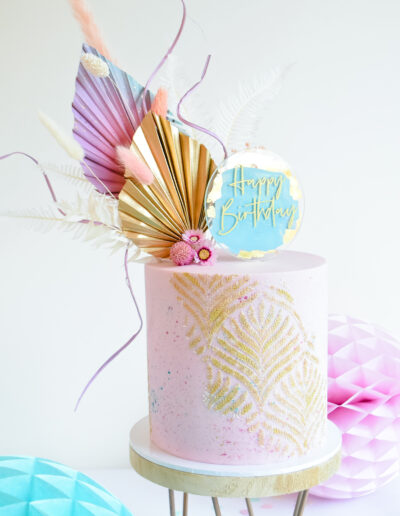 Boho birthday cake with dried blooms and cake topper