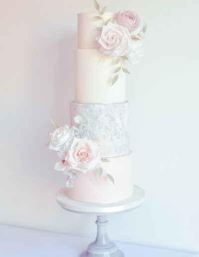 Textured four tier fondant finished cake dressed with hancrafted sugar blooms